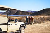 Senior friends on safari watching wildlife in distance