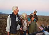 Happy senior couple on safari drinking champagne