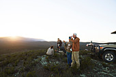 Group drinking tea and enjoying sunrise landscape view