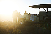 Group drinking tea outside sunny off-road vehicle