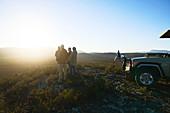 Group enjoying idyllic sunrise from hill South Africa