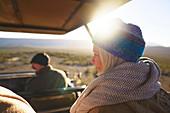 Happy senior woman riding in sunny safari off-road vehicle