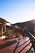 Affectionate couple hugging on sunny safari lodge balcony