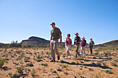 Guide leading group in sunny grassland South Africa