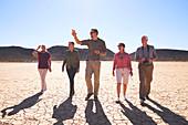 Guide leading group in sunny arid desert South Africa