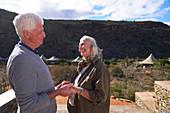 Senior couple on sunny safari lodge balcony South Africa