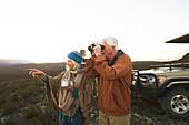 Senior couple with binoculars and tea on safari