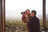 Senior couple with camera on sunny safari balcony
