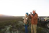 Senior couple on safari using binoculars and drinking tea