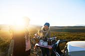 Senior woman on safari pouring tea for friend at sunrise