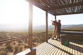 Senior couple looking at view from safari lodge balcony
