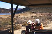 Senior couple on safari watching zebras in distance