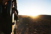 Safari vehicles driving along rock dirt road at sunrise