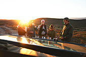 Safari tour group drinking champagne at sunset