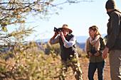 Senior man on safari using digital camera