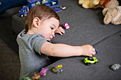 Curious cute toddler girl playing with toy cars on sofa