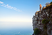 Couple hugging on cliff over sunny ocean