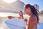 Happy young women friends with surfboards on sunny beach
