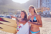 Happy women female surfers with surfboards on sunny beach