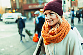 Woman in stocking cap and scarf on urban street