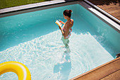 Woman standing in summer swimming pool, reading book