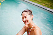 Portrait happy, laughing woman at swimming pool