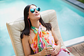 Woman with sunglasses at summer poolside