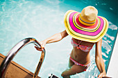 Woman getting out of summer swimming pool