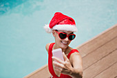 Woman in Santa hat taking selfie at poolside