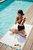 Woman applying sunscreen at summer poolside