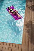 Serene woman relaxing on inflatable raft in swimming pool