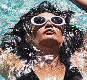 Close up serene woman in sunglasses relaxing, floating