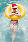 Woman in Santa hat swimming with inflatable ring