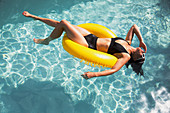 Woman floating on yellow inflatable ring in swimming pool