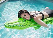 Woman floating on inflatable alligator raft