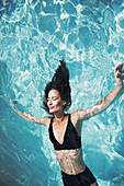Woman floating in summer swimming pool