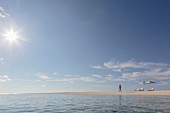 Man walking on sunny, tranquil, remote ocean beach
