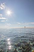 Man standing on sunny, idyllic, remote ocean beach