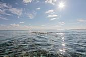 Swimmer splashing in sunny, idyllic ocean, Maldives