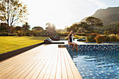 Woman relaxing at sunny, luxury swimming pool