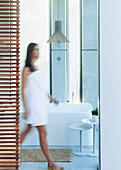 Woman wrapped in a towel walking in luxury, bathroom