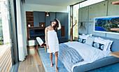 Woman wrapped in a towel walking in modern bedroom