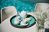 Tea service on poolside patio table