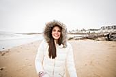 Carefree teenage girl in fur jacket on ocean beach