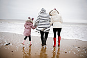 Mother and daughters walking on winter ocean beach