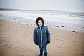 Portrait boy in fur hooded jacket on winter ocean beach