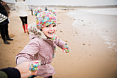 Carefree girl in warm clothing running on winter beach