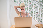 Woman with tattoos working at laptop in kitchen