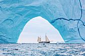 Ship sailing through majestic iceberg arch Greenland