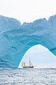 Ship sailing behind iceberg arch on